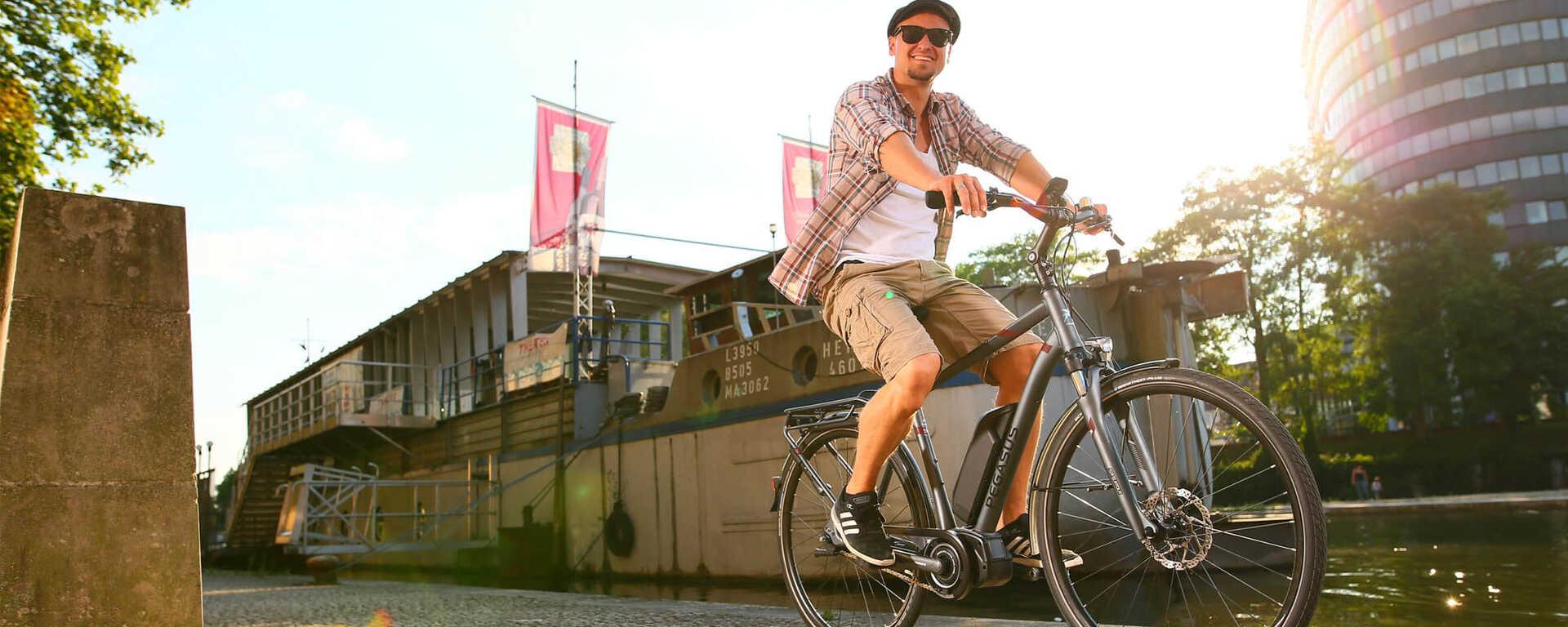 Mann fährt auf einem Pegasus E-Bike durch die Stadt