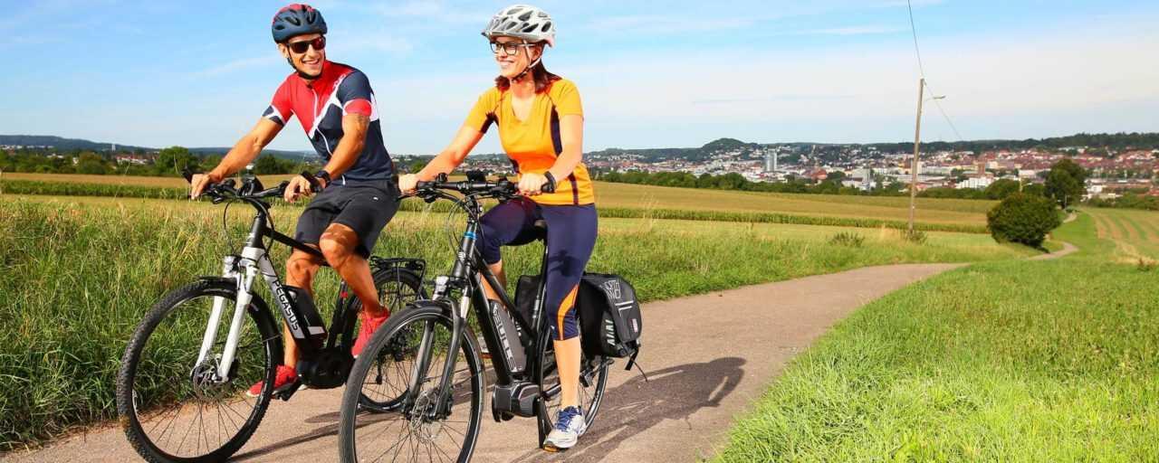 Ein Mann und eine Frau fahren mit Ihren E-Bikes durchs Grüne