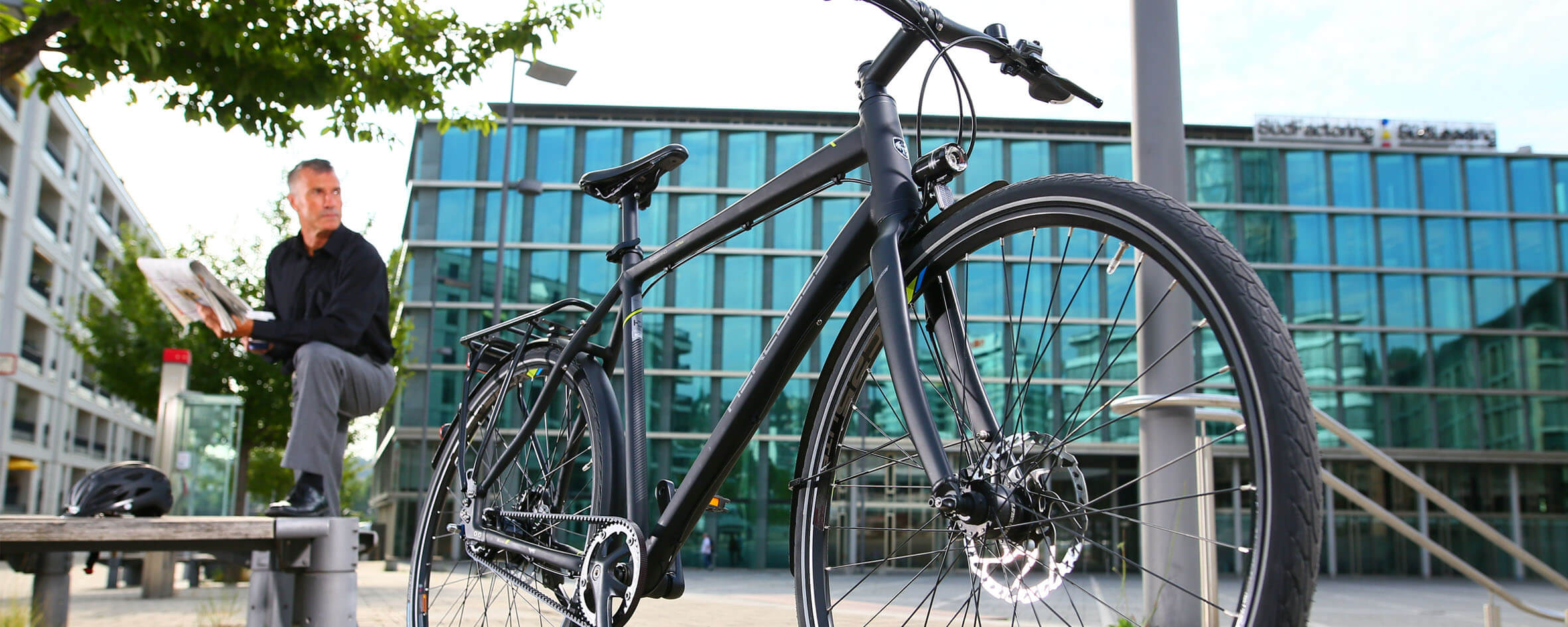 Fahrrad steht vor einem Gebäude. Im Hintergrund steht lessig ein Mann dersein Fahrrad anschaut.