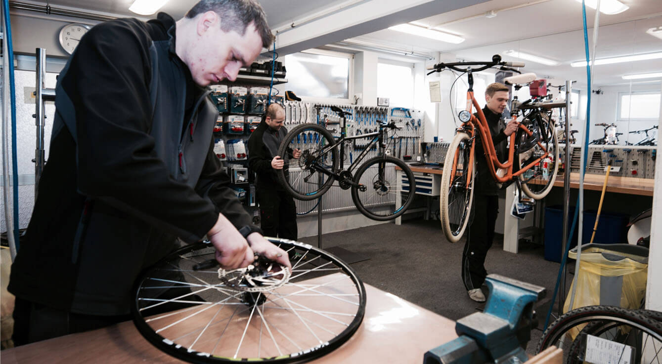 drei Fahrradmechaniker in der Werkstatt reparieren Fahrräder