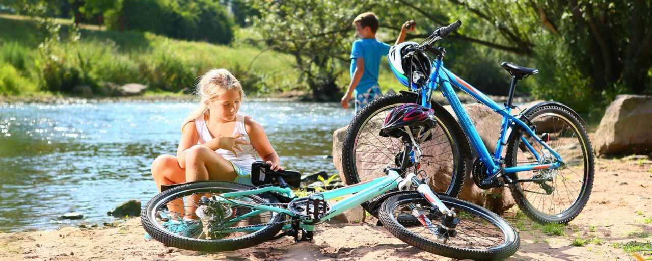 zwei Kinder sind mit Ihren Jugend & kinderfahrrädern an einem Fluss