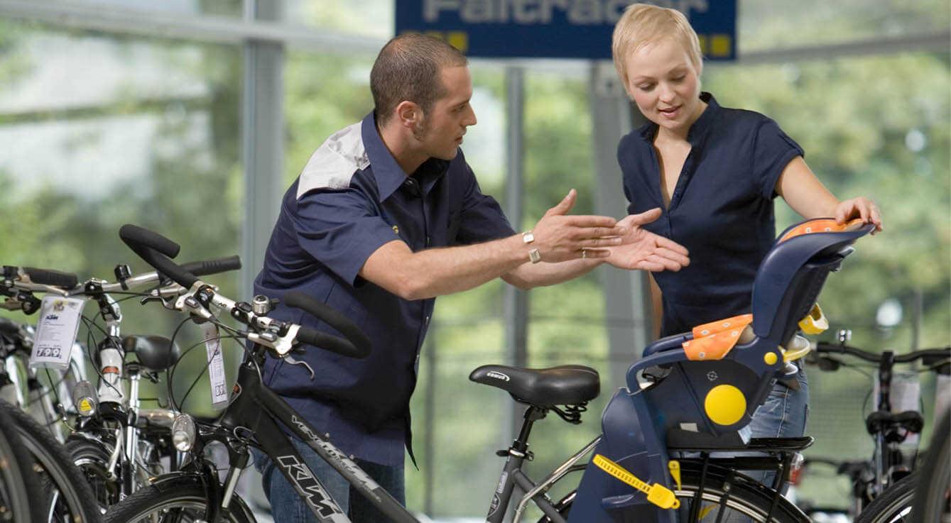 Fahrrad Verkäufer zeigt einer Frau das Fahrrad und berät sie.