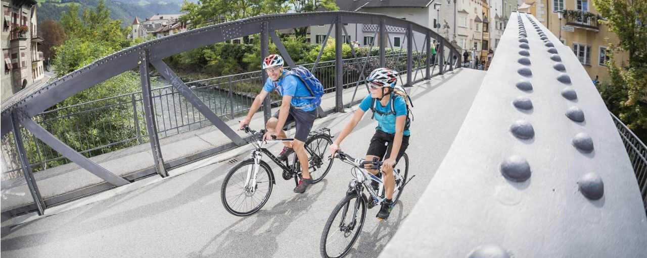 Zwei Personen fahren mit Ihren Trekkingrädern über eine Brücke