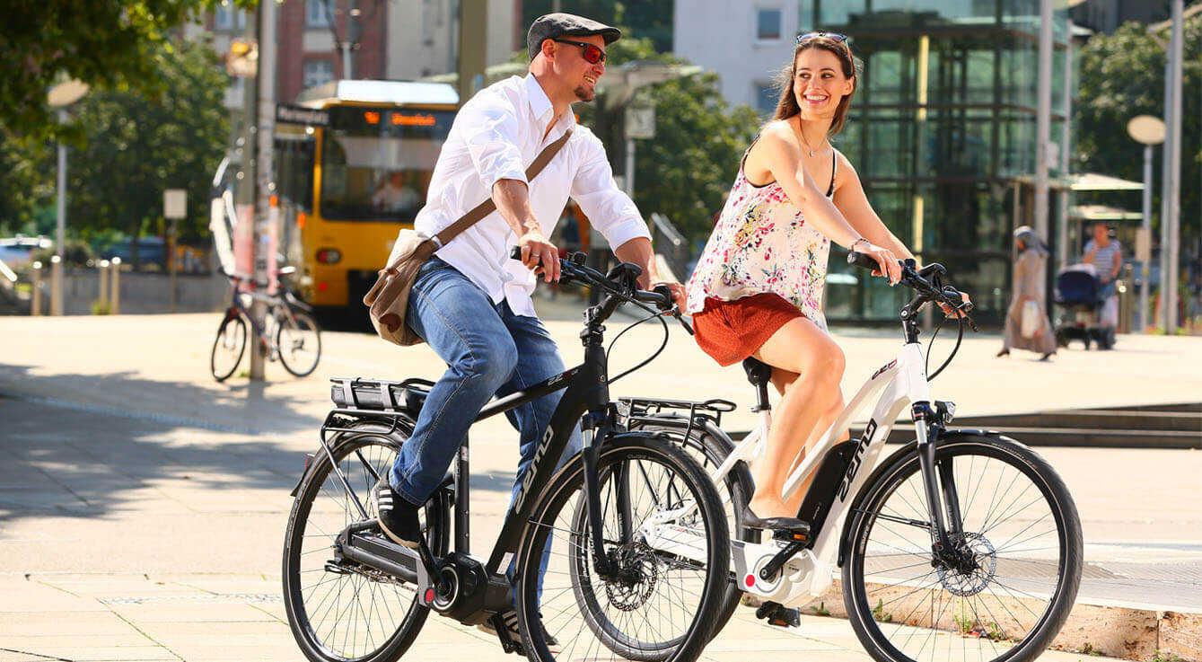 Ein Mann und eine Frau fahren auf E-Bikes durch die Stadt