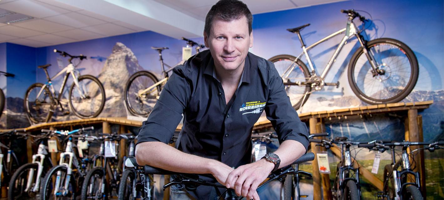 Inhaber Jürgen Schreiber lehnt über einem Fahrrad. Er befindet sich im Fahrradladen
