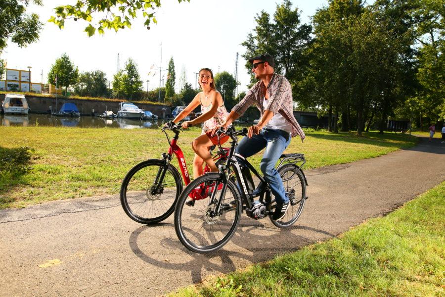 Frau und Mann fahren mit Zemo Pedelecs im Park
