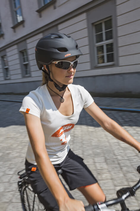 Frau mit Schwarzen Helm fährt durch die Innenstadt
